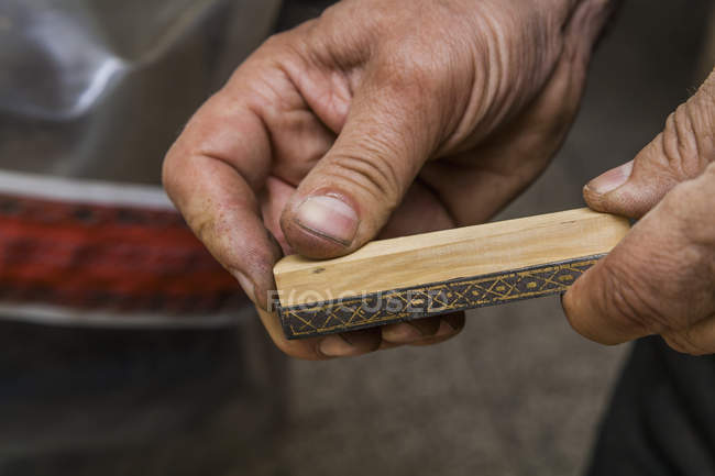 Knife maker holding piece of wood in workshop — Stock Photo