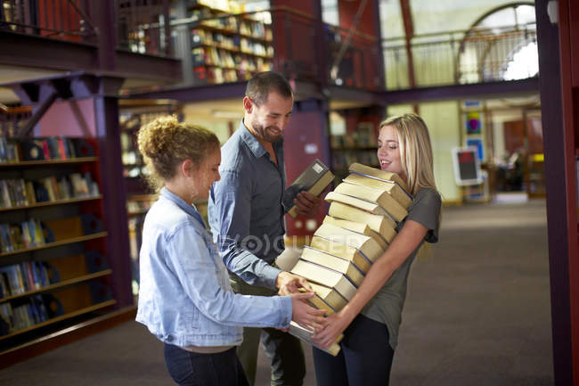 Female student carrying pile of books in a library assisted by friends — Stock Photo