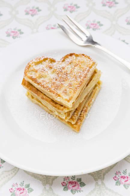 Piatto del cuore a forma di cialde cosparso di zucchero sul panno a velo — Foto stock