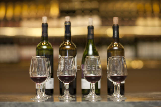 Red wine glasses and wine bottles on a counter of a wine cellar — Stock Photo