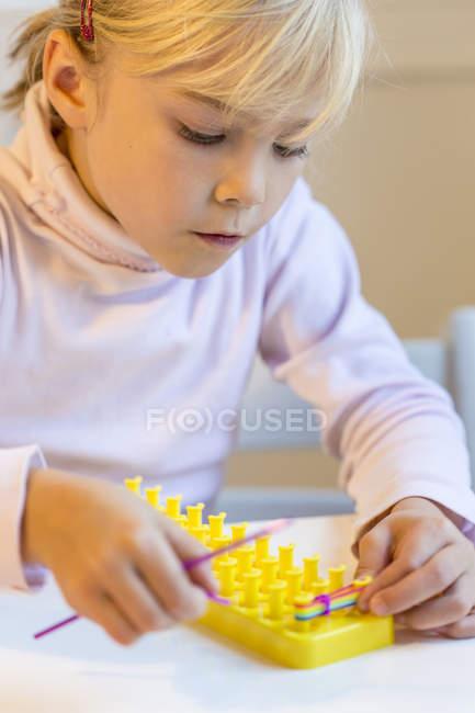 Fille faisant des bracelets avec planche à tisser — Photo de stock