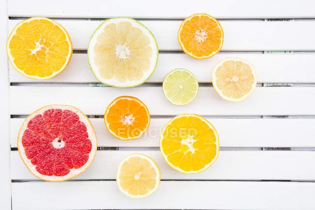 Slices of different citrus fruits on white wood — Stock Photo