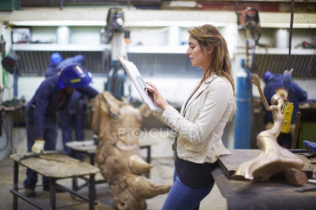 Young woman in a sculptor's workshop checking artwork — Stock Photo