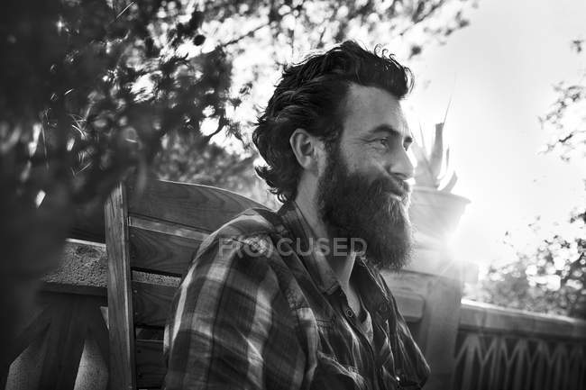 Smiling man with full beard on porch — Stock Photo
