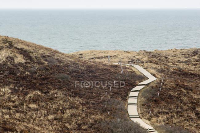 Німеччина, спогади про Шлезвіг-Гольштейн Зільт, дерев'яний тротуар через дюни проти води — стокове фото
