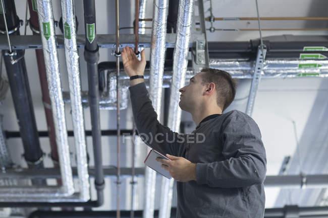 Jovem com tablet digital em sala técnica verificando tubo — Fotografia de Stock