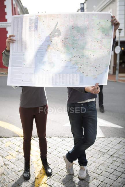 Молода пара, ховаючись за мапі, стоячи на вулиці — стокове фото