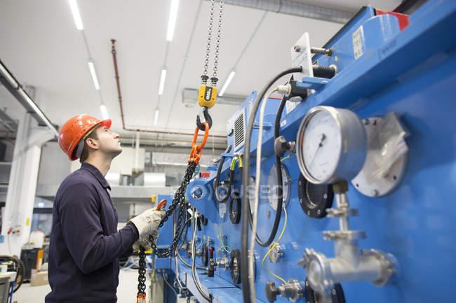Jeune technicien prenant crochet d'un derrick dans le hall industriel — Photo de stock