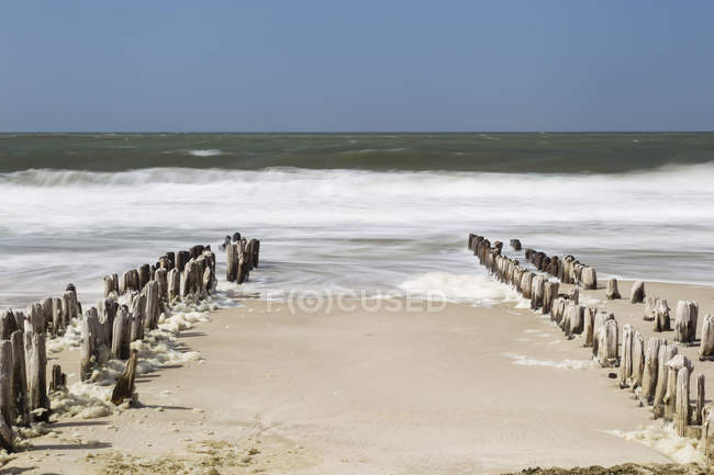 Germany, Schleswig-Holstein, Sylt, North Sea, breakwaters over water — Stock Photo