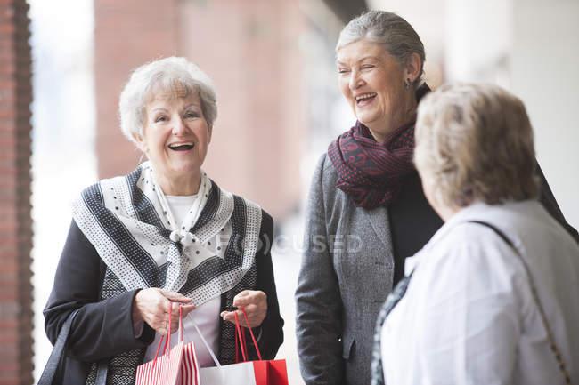 Three laughing senior women on shopping trip — Stock Photo