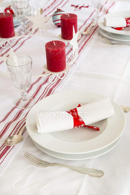 Red-white laid table with candles and crockery — Stock Photo