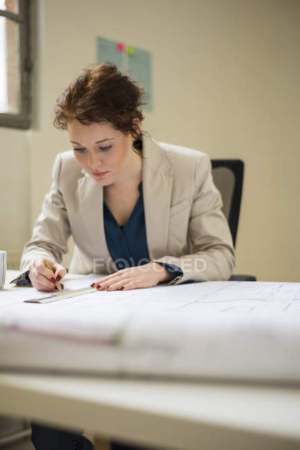Architect working on construction plan in office — Stock Photo