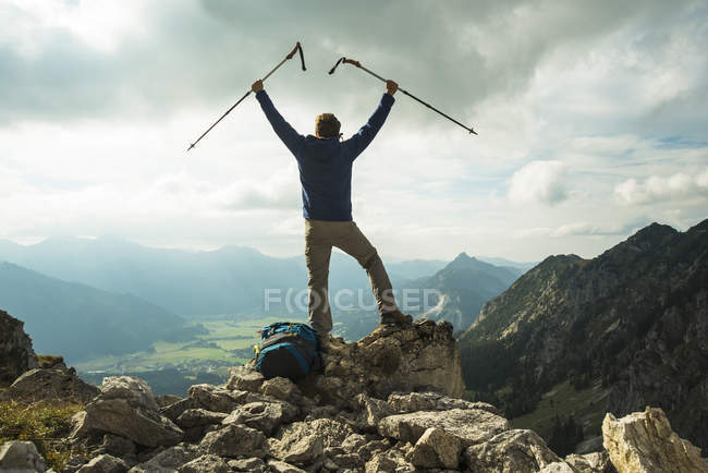 Austria, Tyrol, Tannheimer Tal, young man with hiking poles cheering on mountain top — Stock Photo