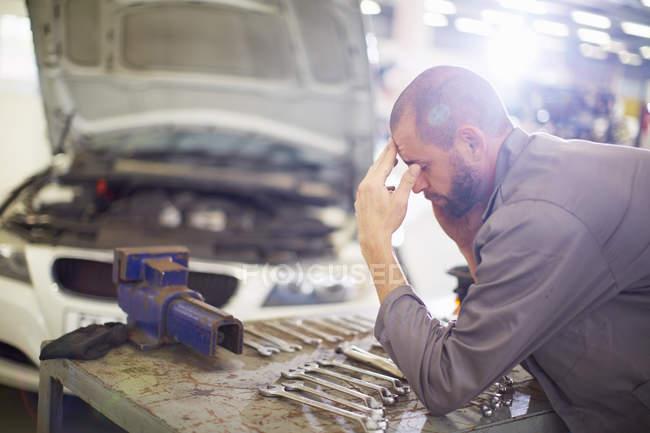 Mecânico de carro estressado na garagem de reparação — Fotografia de Stock