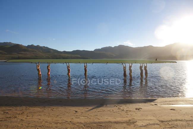 Женская гребная команда поднимает лодку в воду — стоковое фото