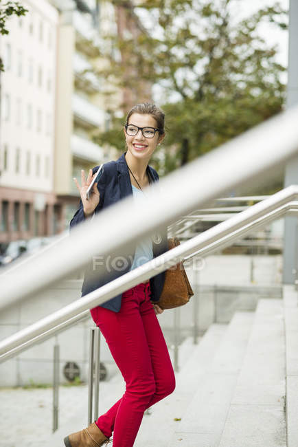 Young smiling businesswoman with smartphone and briefcase waving on stairs — Stock Photo