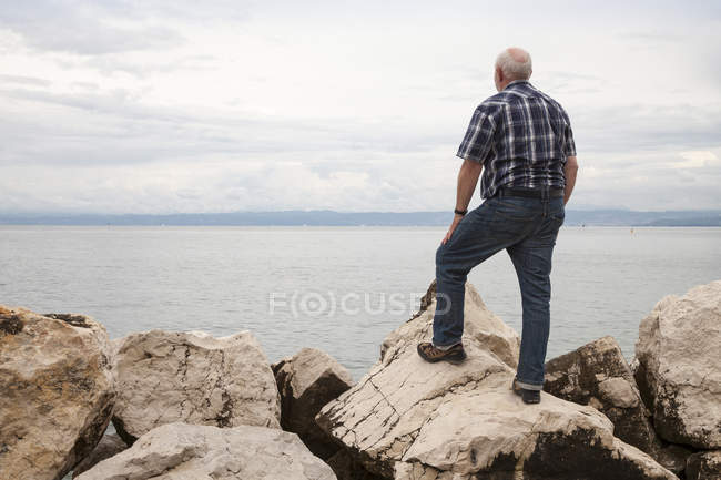 Slovenia, Piran, man standing on rocks at waterside looking at horizon — Stock Photo