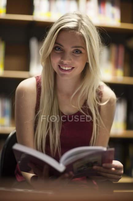 Ученица читает книгу в библиотеке — стоковое фото