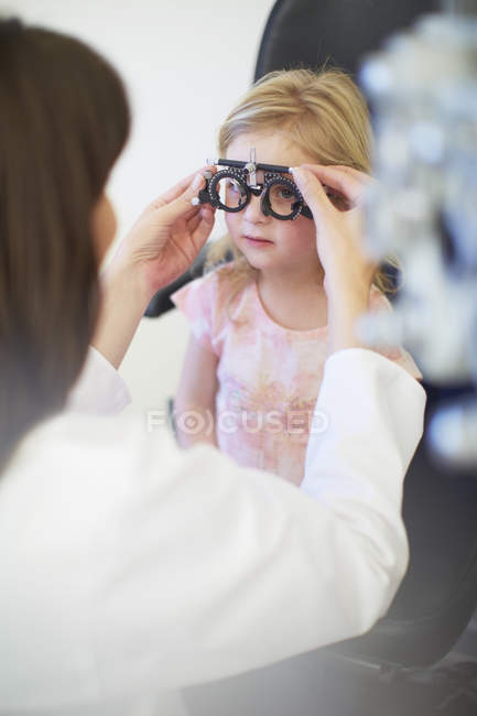 Eye doctor examining girl vision — Stock Photo