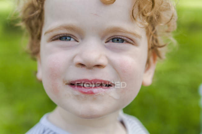 Portrait of smiling little boy covered with ice cream — Stock Photo