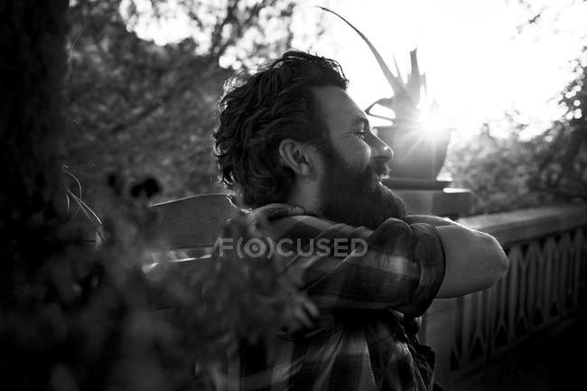 Улыбающийся мужчина с бородой на крыльце — стоковое фото
