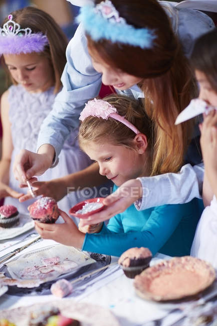 Teenage girl and girls garnishing cupcakes on a birthday party — Stock Photo