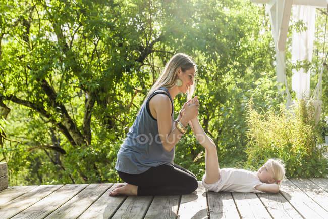Madre e figlia che praticano yoga sulla terrazza in legno — Foto stock