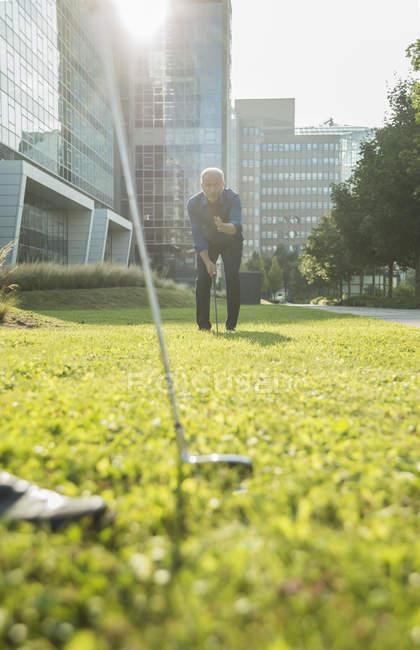 Два бизнесмена играют в гольф возле офисного здания — стоковое фото