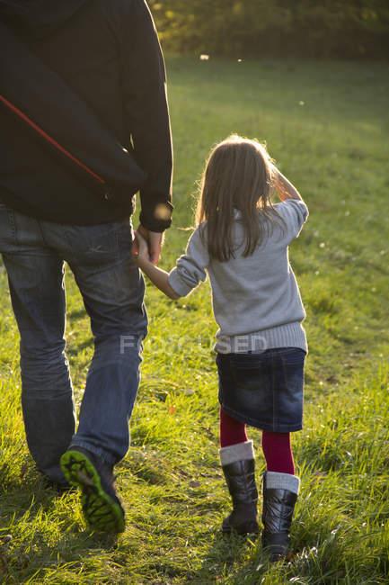 Padre e figlia che camminano sul prato in autunno — Foto stock