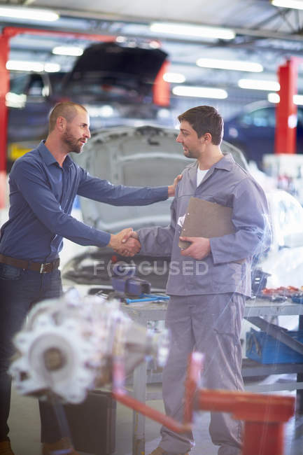 Car mechanic and client shaking hands in repair garage — Stock Photo