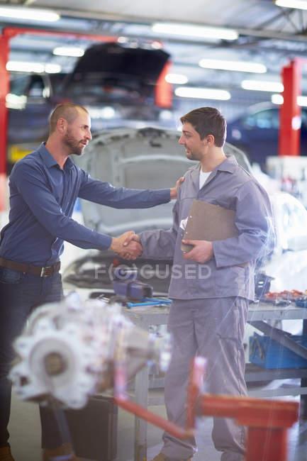 Meccanico auto e cliente stringendo la mano in garage di riparazione — Foto stock