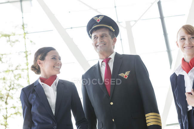 Pilot and flight attendants walking at the airport — Stock Photo