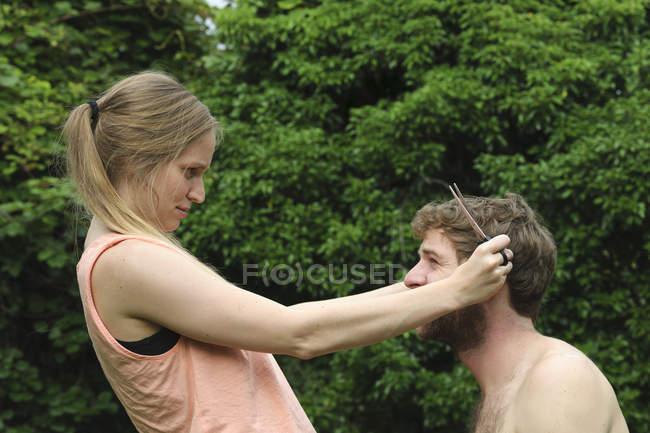 Giovane donna che taglia i capelli del fidanzato in giardino — Foto stock