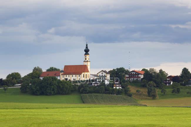 Germany, Bavaria, Upper Bavaria, Chiemgau, Hoeslwang, St. Nicholas 'Church view by the green field — стоковое фото