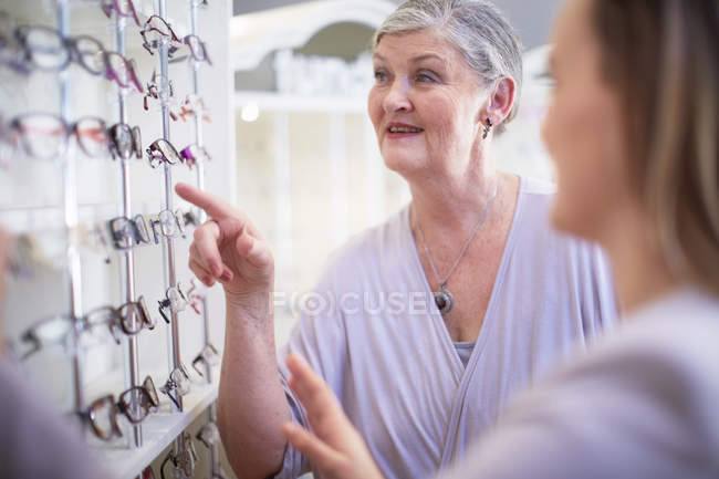 Optician counseling senior woman in shop — Stock Photo