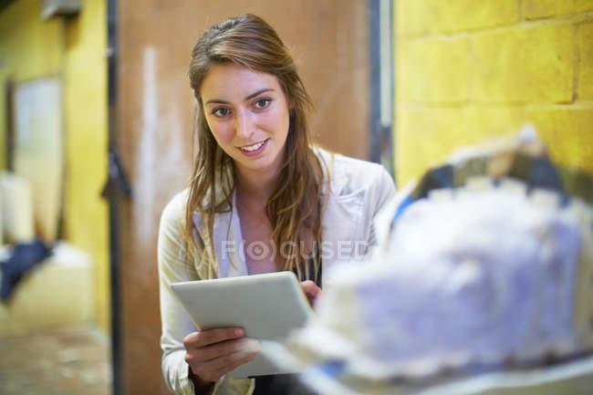 Молода жінка з цифрових таблетку в майстерні скульптора народної — стокове фото