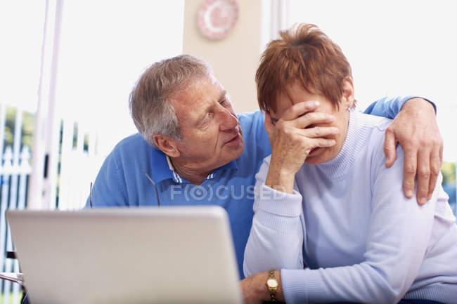 Homem sênior consolando chorando esposa no laptop — Fotografia de Stock