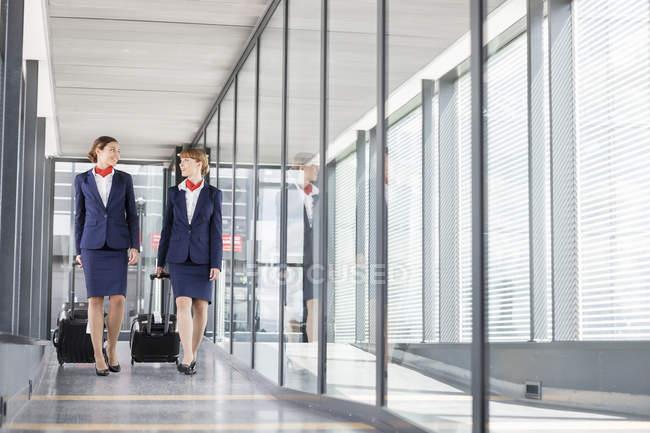 Dos asistentes de vuelo en el pasillo del aeropuerto - foto de stock