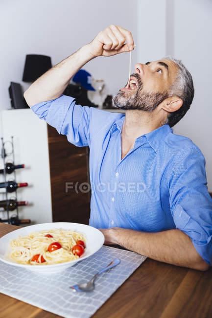 Человек ест макароны в его кухне — стоковое фото