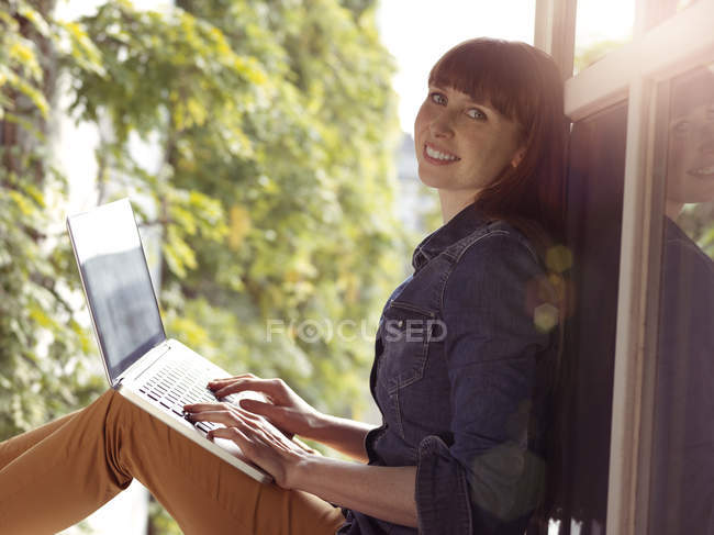 Smiling woman at open window using laptop — Stock Photo