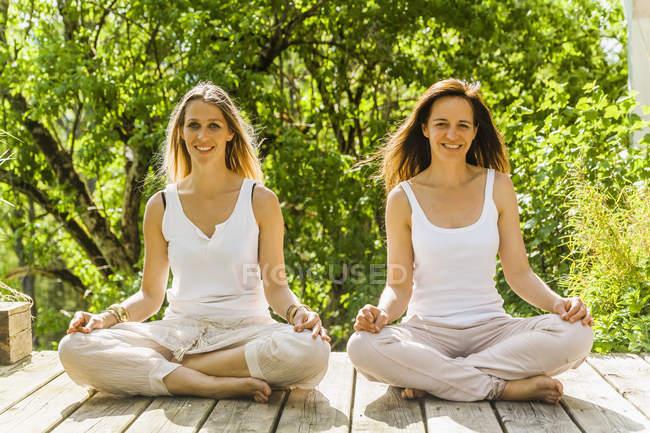 Duas mulheres relaxadas sentadas no terraço de madeira — Fotografia de Stock