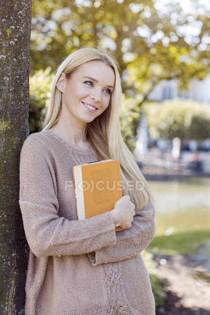 Retrato de jovem sorridente com livro inclinado para tronco de árvore — Fotografia de Stock