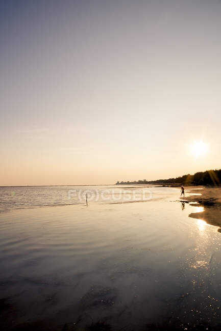 View boy standing to seafront at evening twilight — Stock Photo