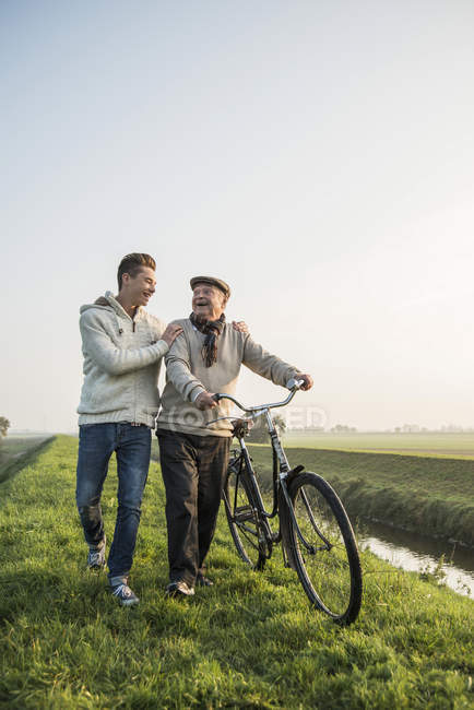 Senior man and grandson in rural landscape with bicycle — Stock Photo