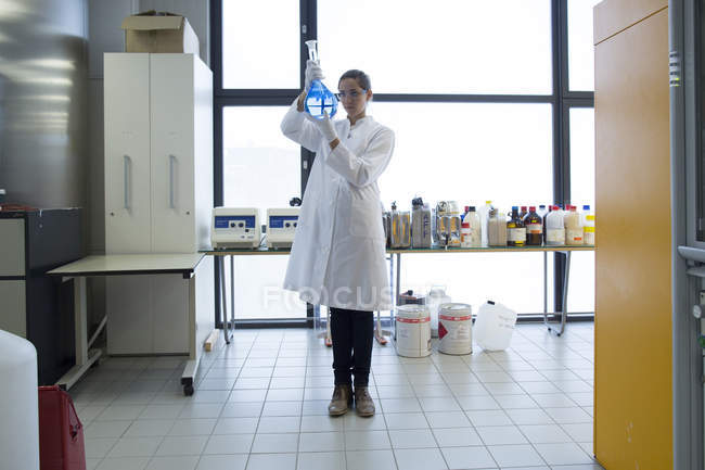 Young female scientist with glass bulb standing in a chemical lab — Stock Photo