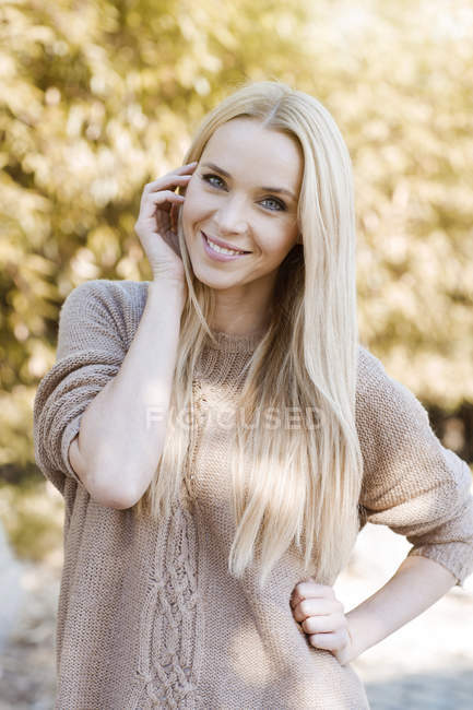 Portrait of smiling young woman wearing knit pullover — Stock Photo