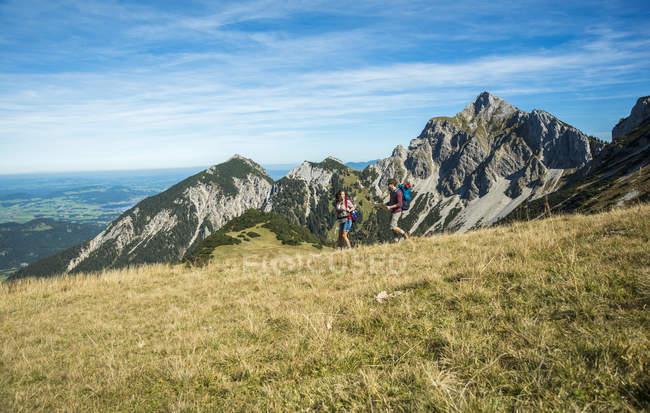 Áustria, Tirol, Tannheimer Tal, caminhadas de casais jovens — Fotografia de Stock