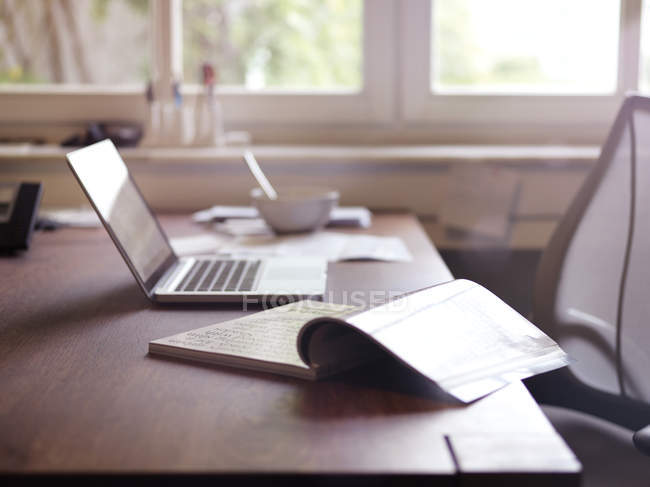 Magazine e portatile sulla scrivania al chiuso — Foto stock