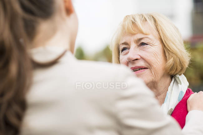 Porträt einer blonden Seniorin, die mit ihrer Enkelin kommuniziert — Stockfoto