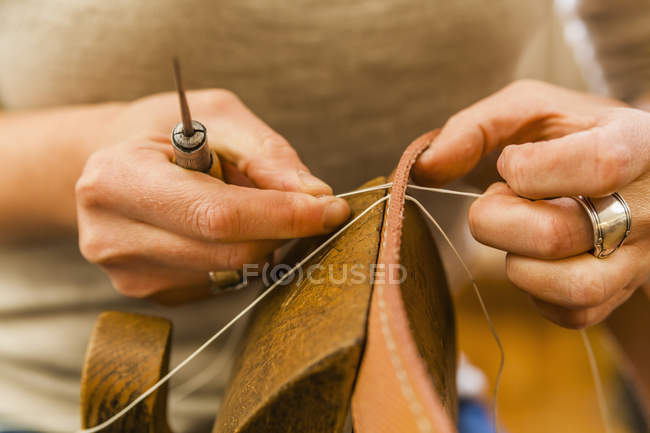 Female hands sewing elastic fabric rubber band using lacing pony and awl — Stock Photo